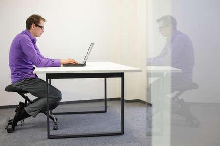 bad sitting posture at workstation  man on kneeling chair