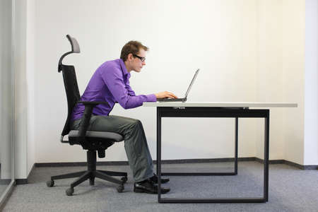 bad sitting posture at laptop . man on chair