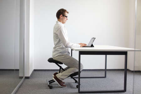 correct sitting position at desk with tablet  man on kneeling chair