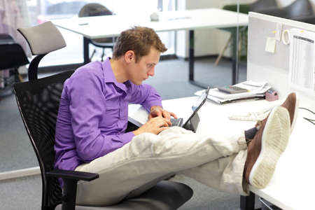 Young businessman caucasian in his office  working with tablet - bad sitting posture