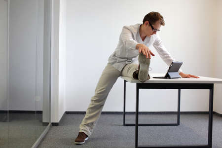 leg exercise durrng office work - man reading at tablet in his office