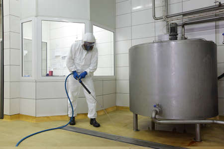 Photo pour worker in white protective uniform,mask,,gloves  with high pressure washer at  large industrial process tank  cleaning floor  in plant - image libre de droit