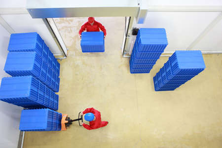 Photo pour Aerial view of two workers working with plastic blue boxes in small warehouse  - image libre de droit