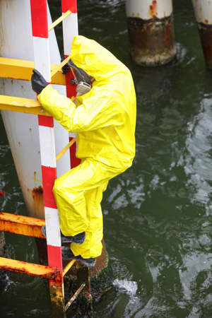 worker in protective suit  climbing ladder over the sea