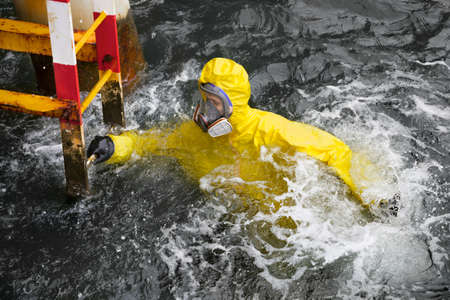 worker in professional, protective suit in ocean water  trying to reach  ladder to save his life