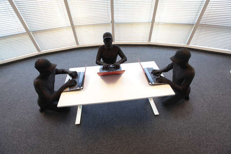 group of anonymous hackers in black costumes working with computers in office