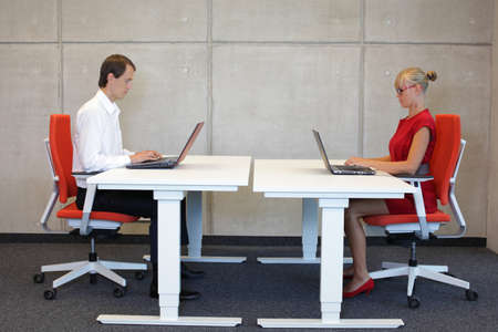 business man and woman working in correct sitting posture with laptops  at electric  height adjustable desks in office