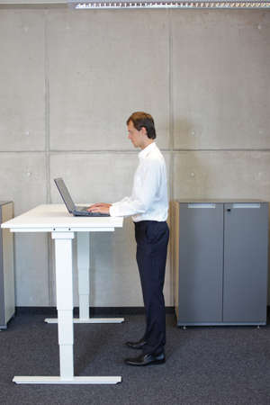 Foto de business man in white shirt standing at electrically controlled height adjustment table, working with tablet - Imagen libre de derechos