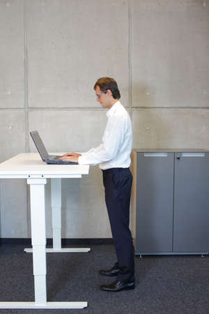 business man with eyeglasses  in white shirt standing at electrically controlled height adjustment table - full extended -  working with tablet