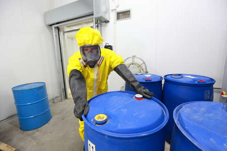 worker in protective uniform dealing with barrels with toxic subsatnce in plant
