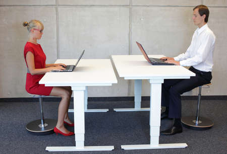 Business men and women working in correct sitting posture with laptops on pneumatic leaning seats at electric height adjustable desks in office