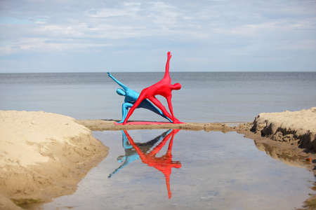 yoga in kaleidoscope at the beach, couple in anonymous colorful costumes
