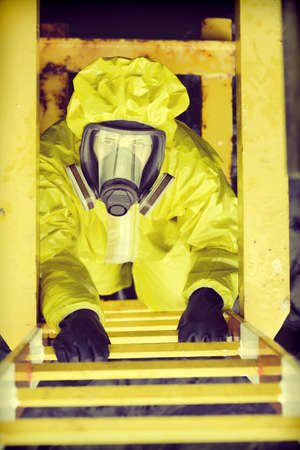 overhead view of specialist in protective suit and mask  on ladder