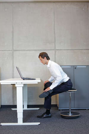 Photo pour Business man exercising on pneumatic leaning seat with laptop at electric height adjustable desk in office - stretching at desk - image libre de droit