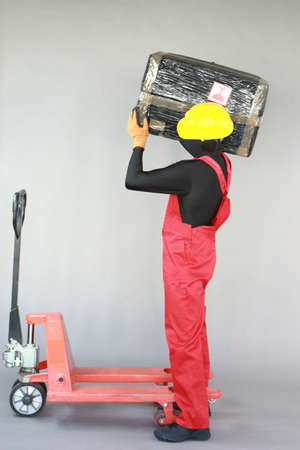 Foto de Anonymous worker carrying heavy package at manual pallet truck.Correct body position.Occupational safety and health. - Imagen libre de derechos