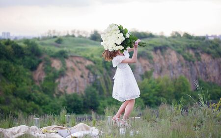 happy girl in a white dress holding a large bouquet of white roses