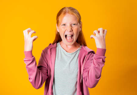 Foto de A young Caucasian redhead girl throws hysterical, angry tantrum, screaming and moving her hands in violent way while having a very angry face. Concept of anger management. People with no self control - Imagen libre de derechos