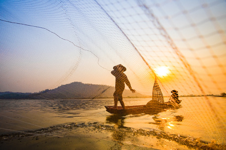 Foto de Fisherman on boat river sunset / Asia fisherman net using on wooden boat casting net sunset or sunrise in the Mekong river - Silhouette fisherman boat with mountain background life person countryside - Imagen libre de derechos