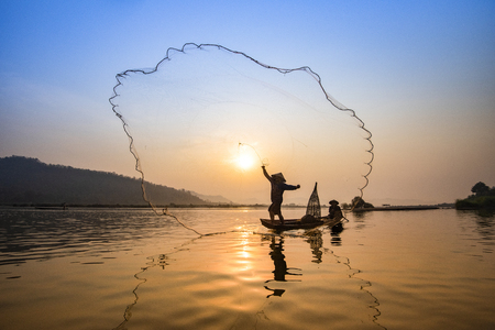 Photo pour Asia fisherman net using on wooden boat casting net sunset or sunrise in the Mekong river / Silhouette fisherman boat with mountain background people life on countryside - image libre de droit