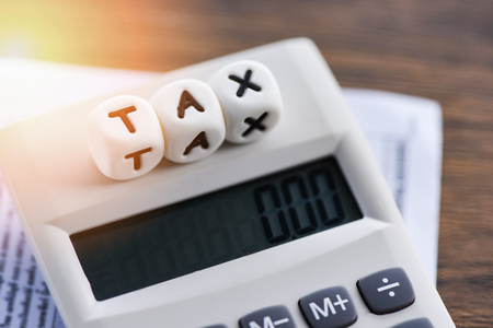 Photo pour Tax words on calculator on invoice bill paper finances for time tax calculation filling paid debt payment at table office business - image libre de droit