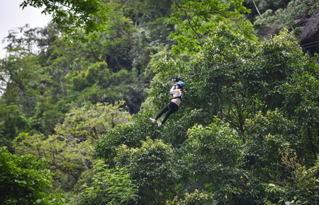 Zipline exciting sport adventure activity hanging on the big tree in the forest at vangvieng laos