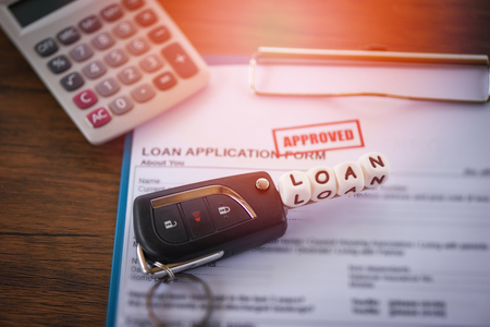 loan approval / financial loan application form for lender and borrower for car with key and calculator on the table office