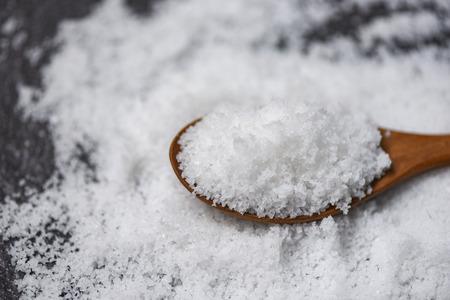 Photo pour Salt in wooden spoon and heap of white salt on dark background - image libre de droit
