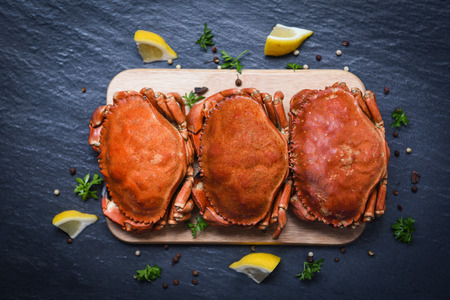 Photo for Cooked crabs on wooden board with lemon on plate served on dark plate top view / stone crab steamed seafood - Royalty Free Image