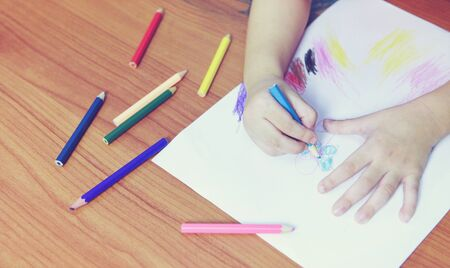 Photo pour Girl painting on paper sheet with colour pencils on the wooden table at home / child kid doing drawing picture and colorful crayon - image libre de droit