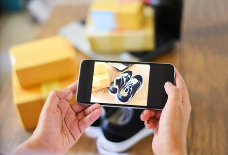 Photo for young woman taking photo sneakers with camera smartphone for post to sell online on the internet market website / selling online ecommerce shipping online shopping delivery and order concept - Royalty Free Image