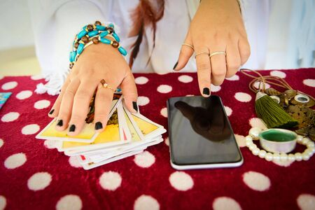 Photo for Fortune teller reading fortune lines on screen smartphone modern horoscopes online fortune telling application Palmistry Psychic readings and clairvoyance hands concept with Tarot cards divination - Royalty Free Image