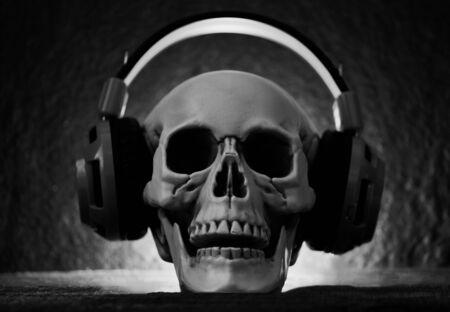 Photo pour Skull music with headphone / Human skull listening to music earphone decorated at halloween party and light on dark background  - image libre de droit