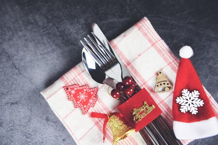 Photo pour Christmas table place setting decoration with santa claus hat fork spoon and knife on tablecloth napkin Xmas New Year food lunch festive Christmas dinner holidays background themed party - image libre de droit