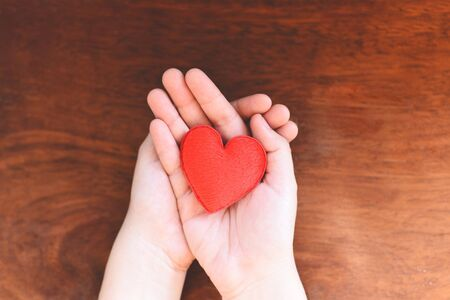 Photo for heart in hand for philanthropy concept / woman holding red heart on hands for valentines day or donate help give love warmth take care with wooden background  - Royalty Free Image