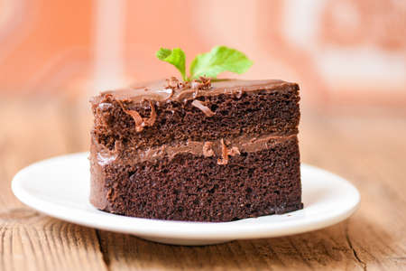 Photo pour Cake chocolate delicious dessert served on the table / cake slice on white plate with topping chocolate and mint leaf - image libre de droit