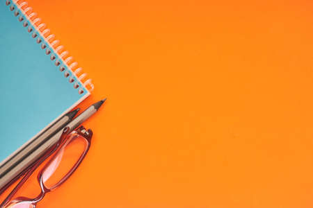notebook with eyeglasses and pencils on orange background
