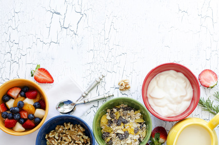 Fresh fruit salad, nuts, yogurt and granola for breakfast, close-up, top view, horizontal background, copy space
