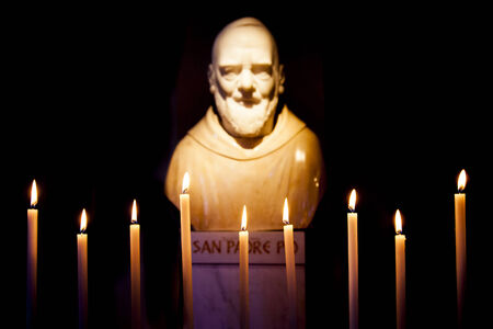 Padre Pio statue with candles isolated on black background