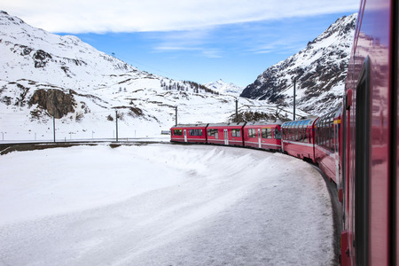 Bernina Express train, one of the highest railway in the world, goes across snowy mountain between Italy and Switzerland