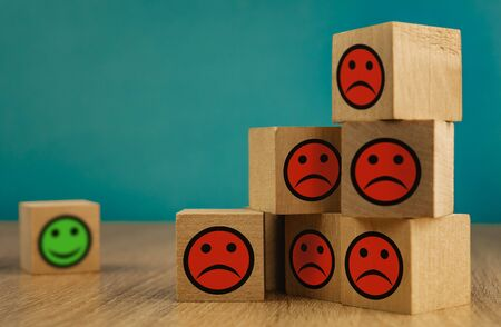 Photo for smiling and sad emoticons on a blue background. satisfaction concept. - Royalty Free Image