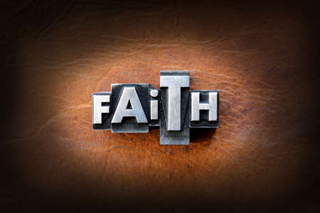 The word faith made from vintage lead letterpress type on a leather background.