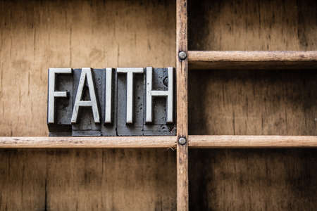 The word FAITH written in vintage metal letterpress type sitting in a wooden drawer.