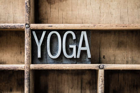 The word \YOGA\ written in vintage metal letterpress type sitting in a wooden drawer.