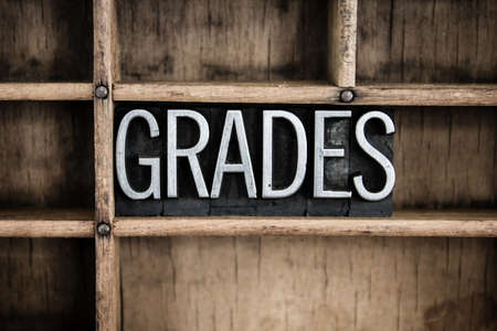 The word GRADES written in vintage metal letterpress type in a wooden drawer with dividers.