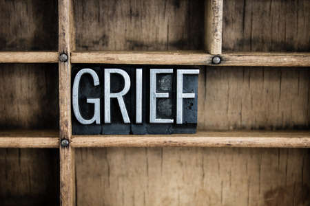 The word GRIEF written in vintage metal letterpress type in a wooden drawer with dividers.