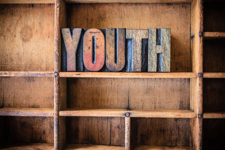 The word YOUTH written in vintage wooden letterpress type in a wooden type drawer.