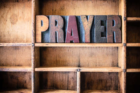 The word PRAYER written in vintage wooden letterpress type in a wooden type drawer.