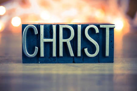The word CHRIST written in vintage metal letterpress type on a soft backlit background.