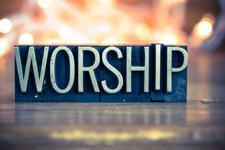 Photo for The word WORSHIP written in vintage metal letterpress type on a soft backlit background. - Royalty Free Image
