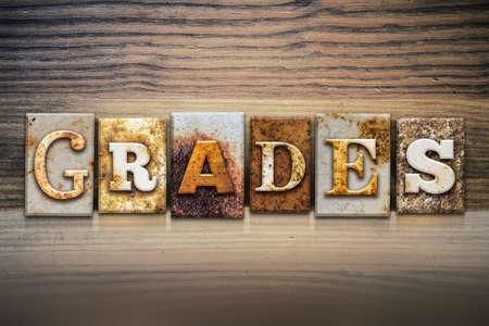 The word GRADES written in rusty metal letterpress type sitting on a wooden ledge background.